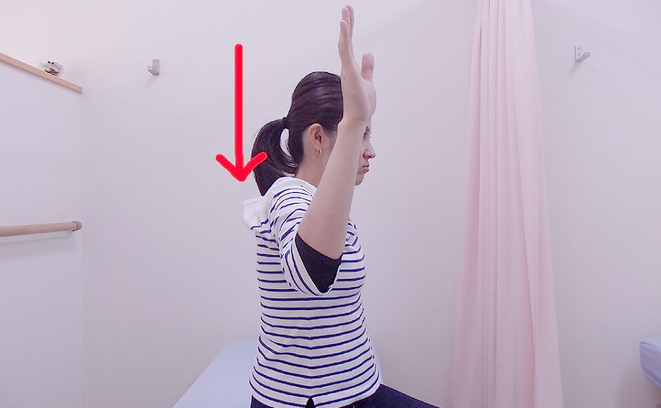ゆっくり腕を下ろす女性