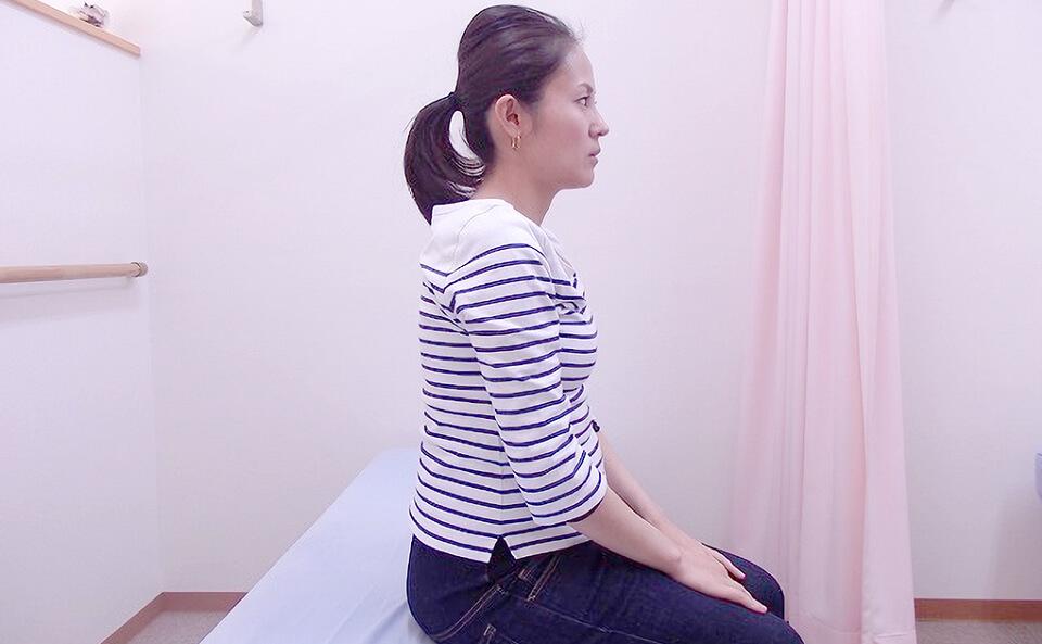 太ももの上に手を置いて肩の力を抜く女性