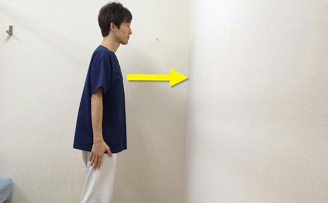 壁を正面に真っすぐ立つ