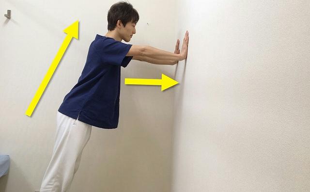 肘を伸ばして両手を壁につける
