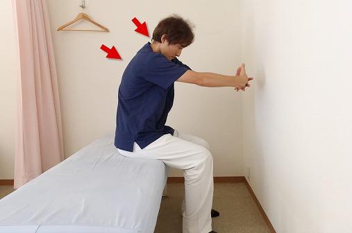 手を前で組んで押し出すように伸ばす