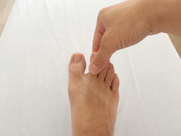 足の指をつまむ